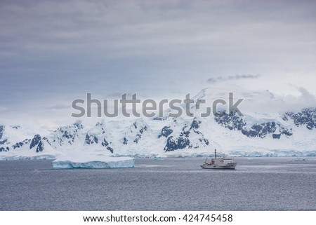 Expedition ship next to a glacier in Antarctic peninsula during Antarctic summer - stock photo