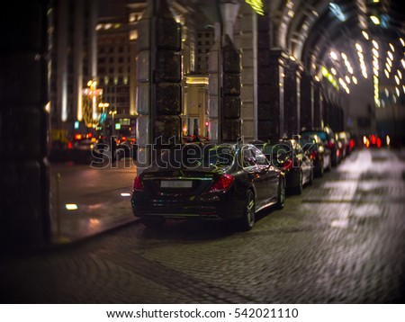 Expensive cars at the entrance to the Ritz Carlton Moscow with the view on Tverskaya street in night