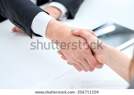 Expensive deal. Confident and successful two businessmen shaking hands at the signing. The man shakes hands with a woman at business lunch - stock photo