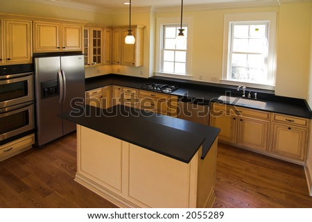 Expensive kitchen with island and appliances - stock photo