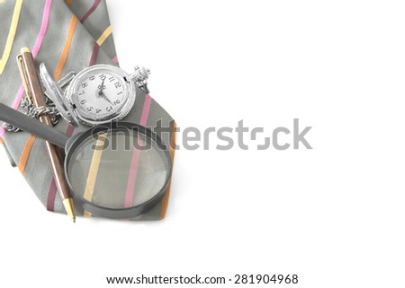 Expensive pen, pocket watch and magnifier glass on top of vibrant strip color gray necktie over white background