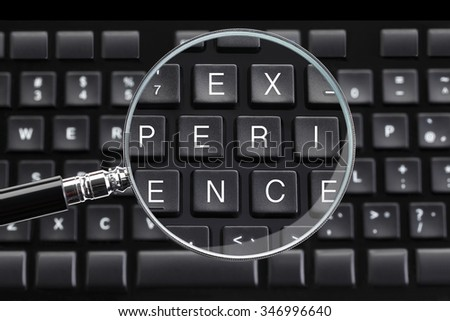 EXPERIENCE written on keyboard with magnifying glass