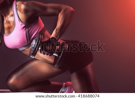 experienced athlete, coach, performing exercises on arm muscles using dumbbells. black background, studio. African-American. black shorts, a pink top. - stock photo