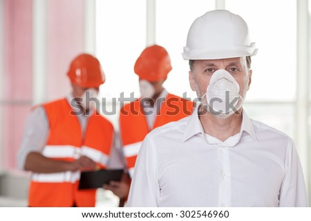 Experienced builders are in process of building. The old architect is standing in mask and looking at the camera seriously. Workers are standing behind him and reading documents with concentration - stock photo
