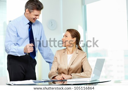 Experienced businessman explaining some business matters to his positively looking trainee - stock photo