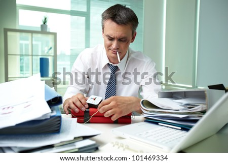Experienced businessman surrounded by big heaps of papers making dynamite
