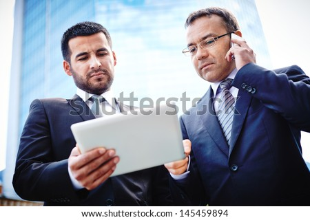 Experienced businessmen discussing details of the project and negotiating with their client on the phone - stock photo