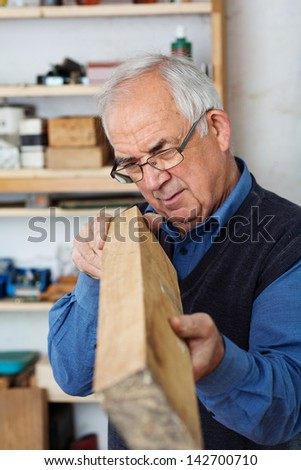 Experienced carpenter checking the edges of a wood piece. - stock photo