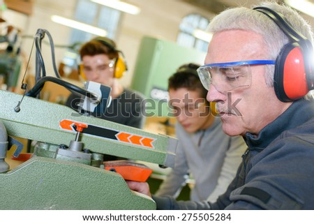 Experienced carpenter teaching two teenage boys - stock photo
