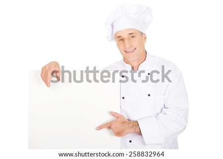Experienced chef in white uniform holding empty banner. - stock photo
