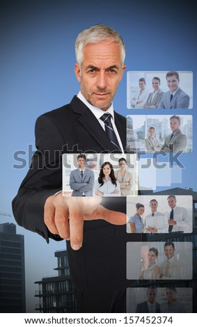 Experienced classy businessman using digital interface showing coworkers