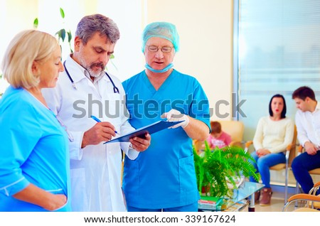 experienced doctor and medical staff consulting about health record in hospital