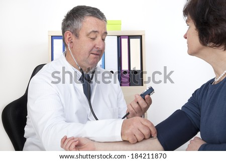 Experienced Doctor measures blood pressure - stock photo