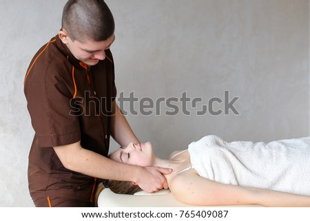 Experienced doctor professionally kneads neck and conducts therapeutic procedure for neck, removes discomfort of young woman who lies on couch, covered with terry towel. Man of European appearance