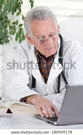 Experienced doctor researching on internet in his office  - stock photo