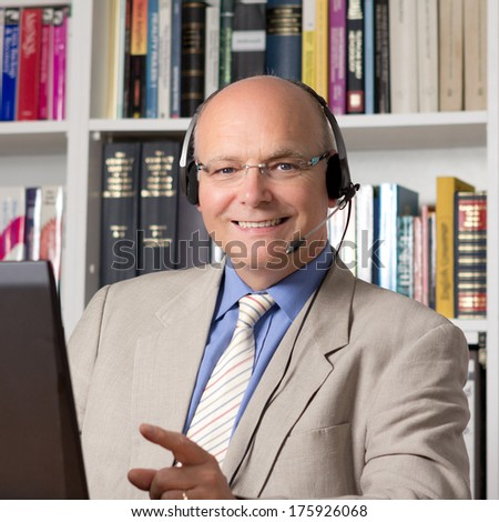 Experienced employee of customer service with headphones smiling happily - stock photo