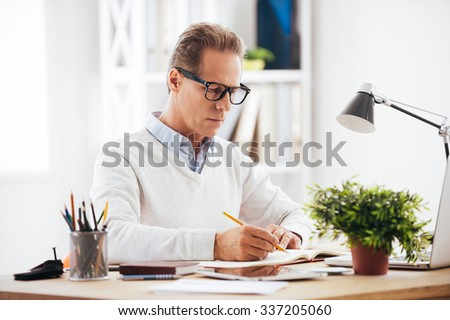 Experienced expert at work. Confident mature man writing something in his notebook while sitting at his working place - stock photo