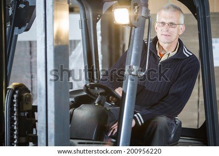 Experienced forklift driver is posing inside his forklift in a warehouse - stock photo