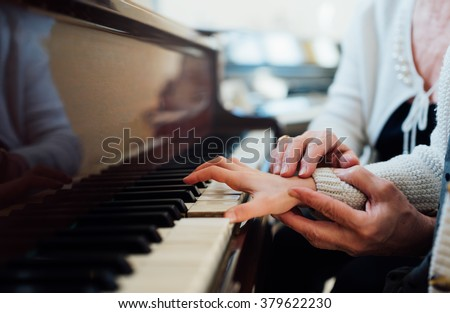 experienced hand of the old music teacher helps the child  pupil