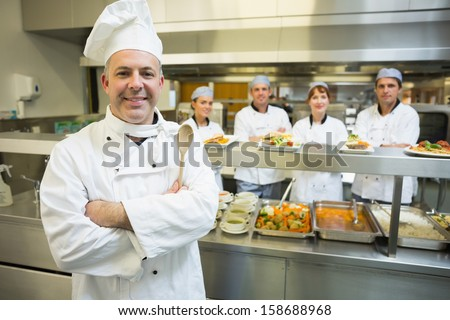 Experienced head chef posing proudly in a modern kitchen with his team in the background - stock photo