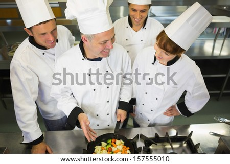 Experienced head chef showing pan to his colleagues in kitchen - stock photo