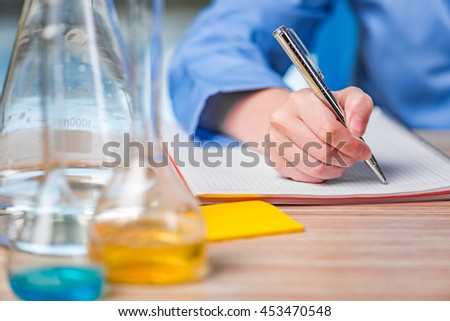 Experienced lab assistant working on chemical solutions - stock photo