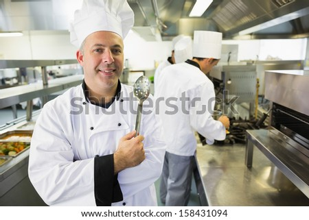Experienced male chef posing in a kitchen holding a slotted spoon