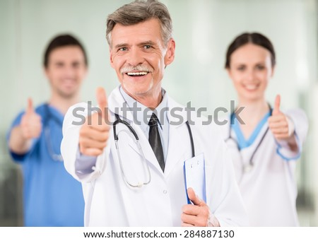 Experienced male doctor with colleagues looking at camera and smiling. - stock photo
