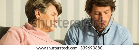 Experienced male physician examining with stethoscope older woman