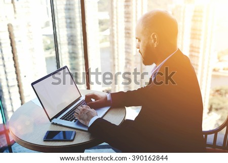 Experienced man trader is analyzing financial market via laptop computer, while is sitting in modern office interior. Male skilled accountant is checking the validity of the operation via net-book - stock photo