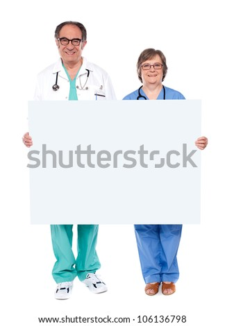Experienced medical professionals showing blank billboard. Full length portrait