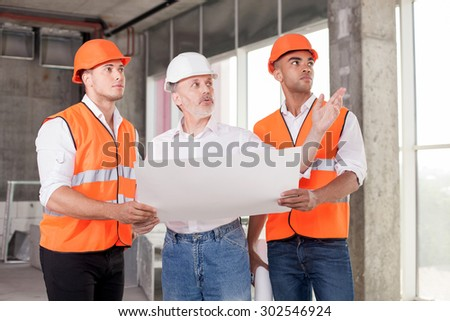 Experienced old architect is explaining to young workers his ideas of building. He is pointing his arm sideways seriously. The men are holding a blueprint and looking aside with concentration - stock photo