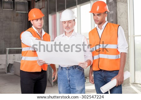 Experienced old architect is holding blueprint. The young foreman is pointing finger at sketches with seriousness and explaining concepts of building. The workers are looking at it with concentration