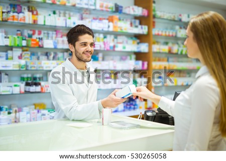 Experienced pharmacist counseling female customer in modern pharmacy