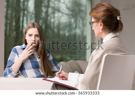 Experienced psychiatrist diagnosing teenage girl with mental problem