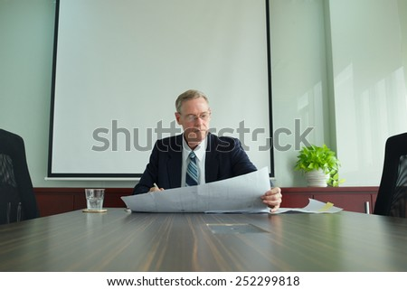 Experienced real estate agent examining plan of the building