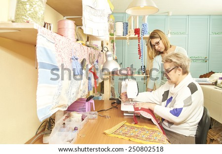 Experienced seamstress is teaching her assistant to work on sewing machine at workshop