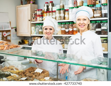 Experienced seller and young assistant at confectionery display with pastry - stock photo