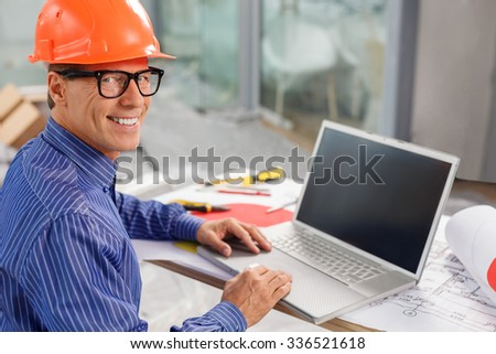 Experienced senior architect is designing a new construction. He is sitting at the desk and using a laptop. The man is looking at camera and smiling - stock photo