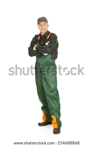 Experienced smiling gardener standing with folded arms - stock photo