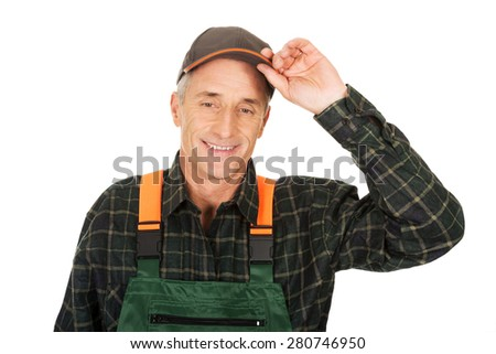 Experienced smiling gardener with protective hat - stock photo