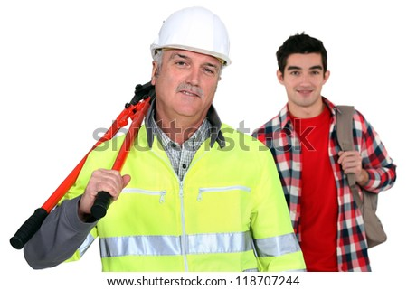 Experienced tradesman posing with his new apprentice - stock photo