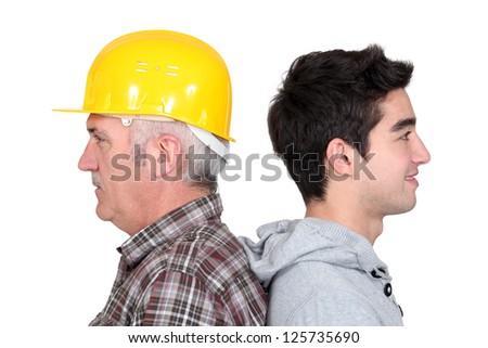 Experienced tradesman standing back to back with his new apprentice - stock photo