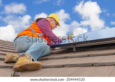 experienced worker checking solar panels on house roof - stock photo