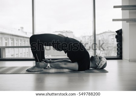 Experienced yoga man doing various  pose and stretching exercises indoors, panoramic city view at background