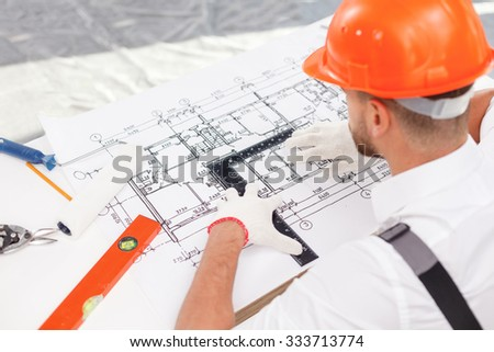 Experienced young builder is working on new project. He is looking at sketch of construction with seriousness. The man is sitting at table and holding a ruler - stock photo