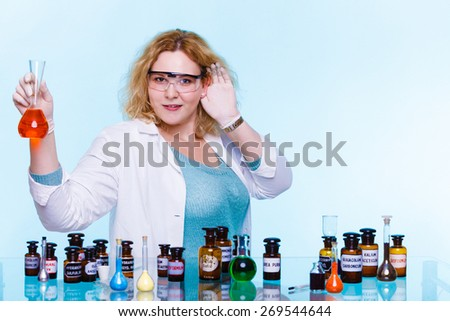 Experiments in laboratory. Chemist woman or student girl, scientific researcher with chemical glassware holding hand to ear listening on blue - stock photo