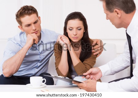 Expert advice. Thoughtful young couple sitting on the couch while confident financial advisor explaining something and pointing clipboard - stock photo