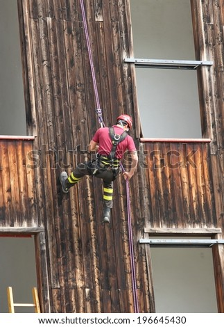 expert firefighter climber down into the wall of the House - stock photo