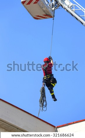 expert firefighter down with the rope in the building during a fire alarm in the fire station - stock photo